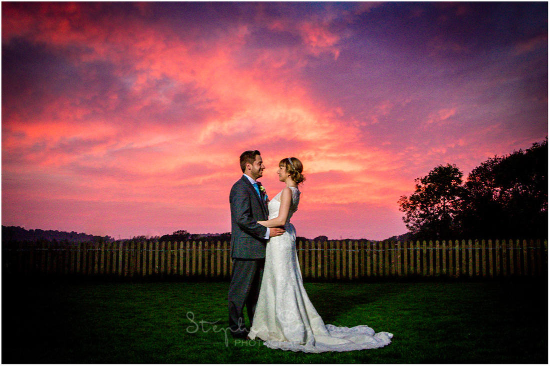 Bride and groom in front of colourful sunset