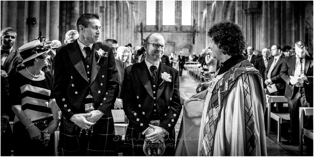 Groom with best man and vicar as the bride arrives at the back of the church