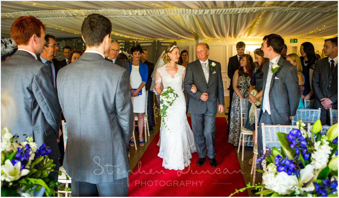 The bride walks down the aisle on her father's arm at the start of the wedding ceremony