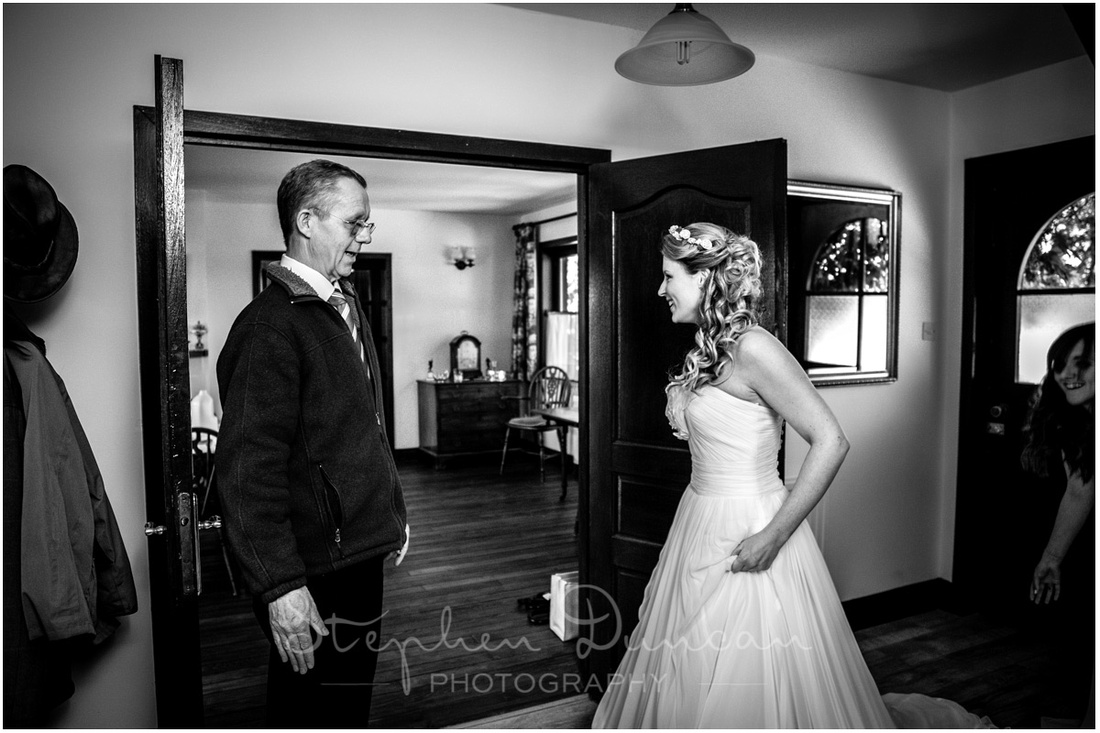 Full prepared, the father of the bride sees his daughter in her dress for the first time