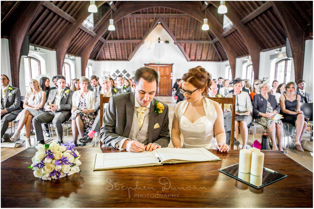 Bride and groom sign the marriage register