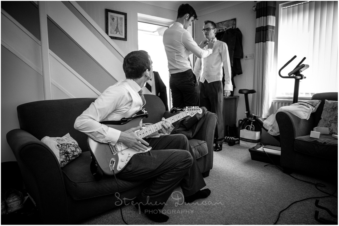 Black and white photo of groom, best man and usher grappling with cravats and guitars