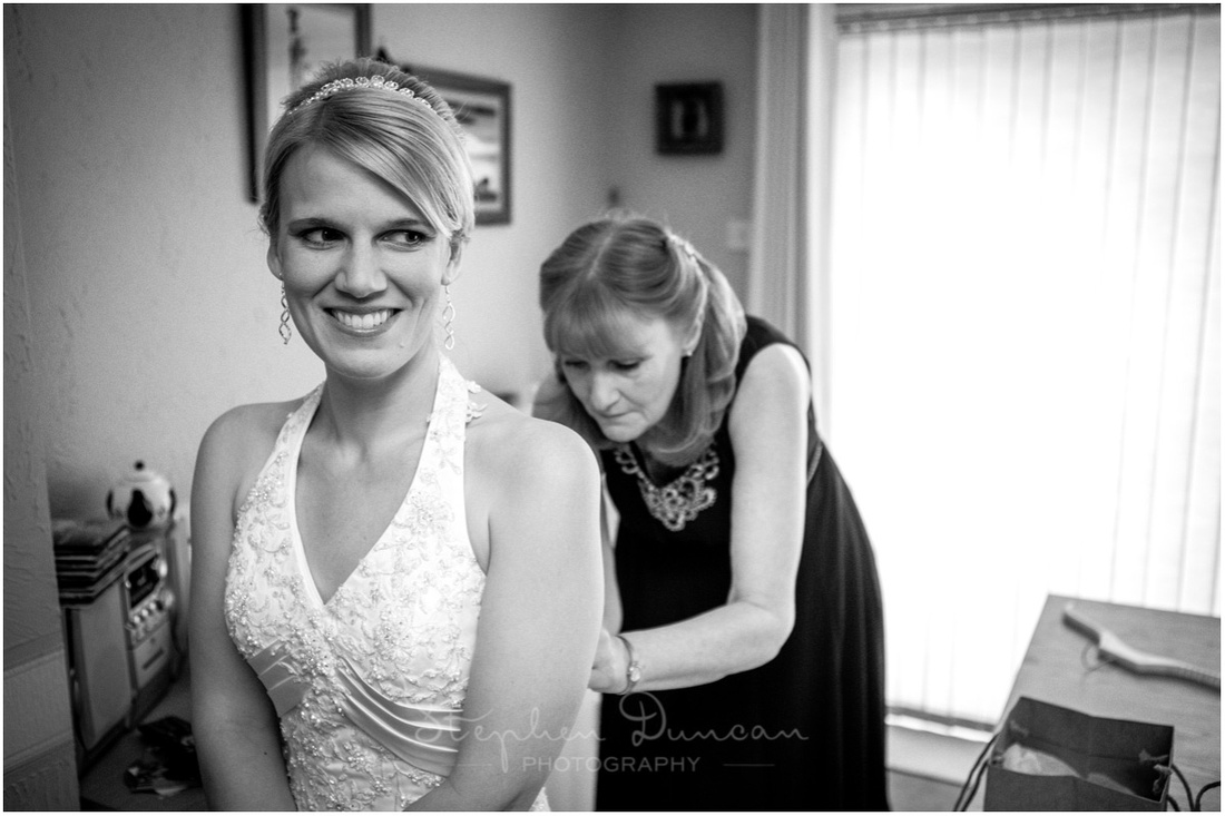 The bride's mother helps to lace up the wedding dress