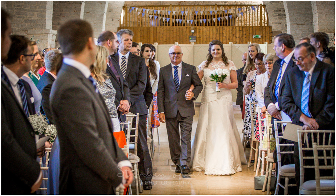 The bride walks down the aisle at the start of the wedding ceremony on her father's arm