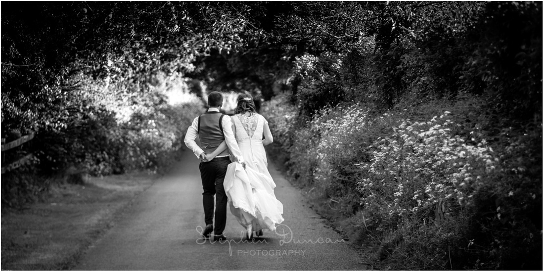 The newly married couple walk along one of the lanes deep in the countryside where the barn is located