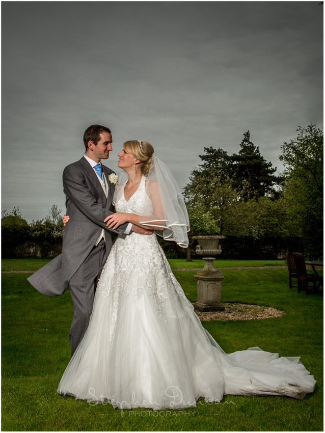 Flash-lit photograph of bride and groom in early evening as dark skies start to encroach, by the manor House at Norton Park Hotel