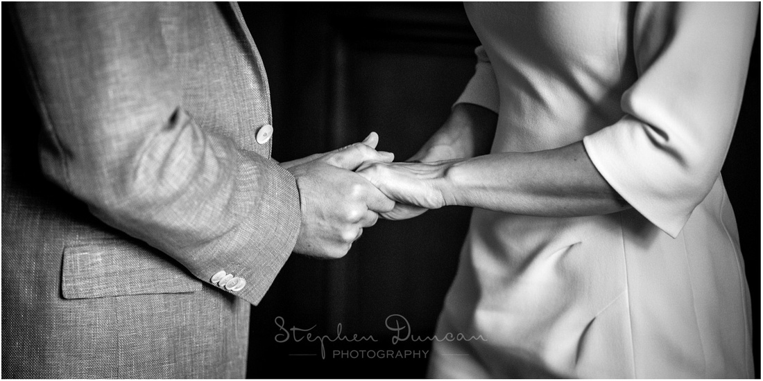 Black and white photo of bride and groom holding hands as they exchange their vows in the Basing Room