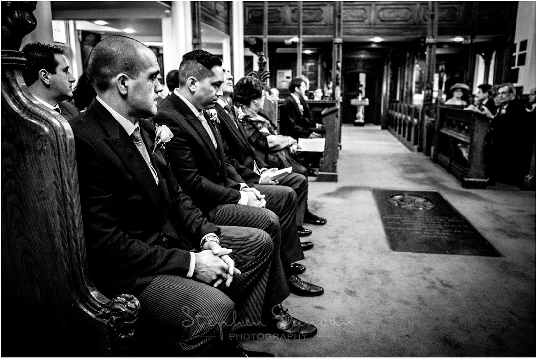 Groom and best man sat in pews at the front of the church