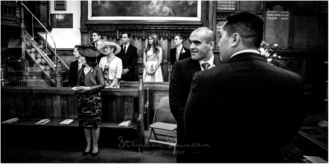 The groom looks over his shoulder and down the aisle as the bride makes her entrance