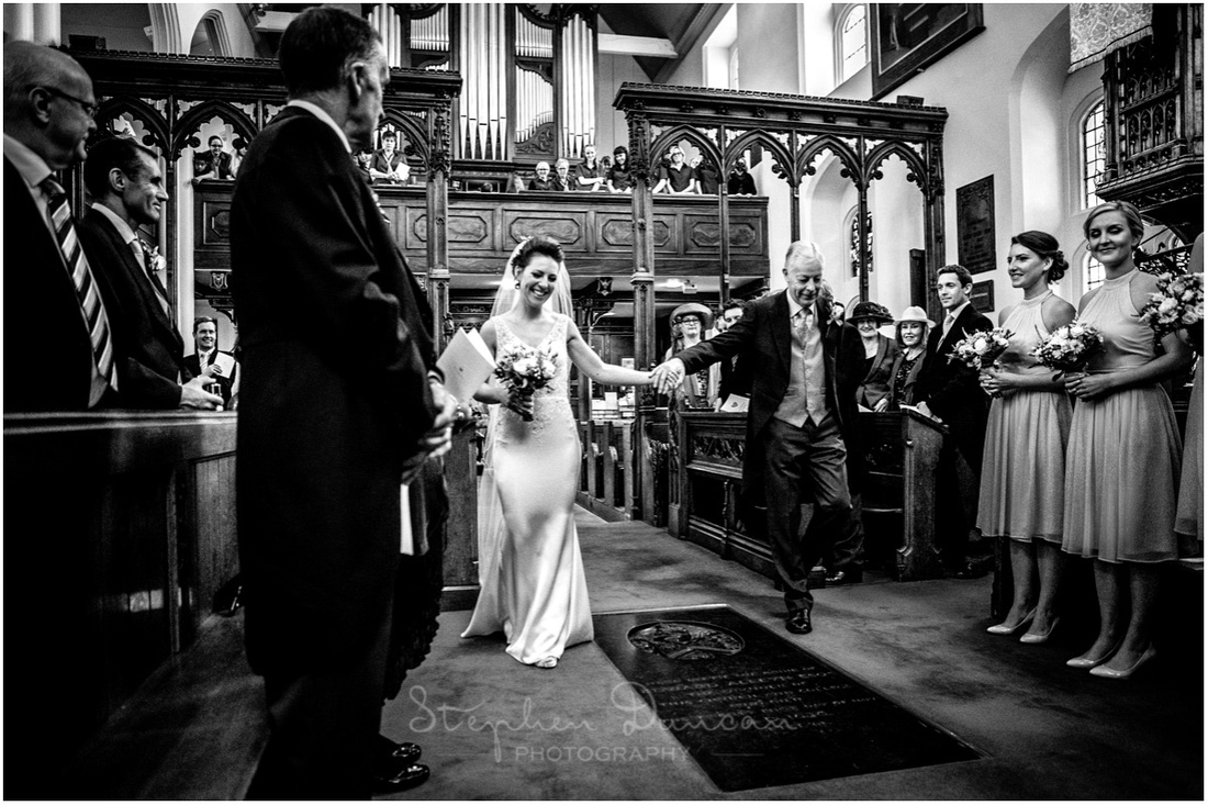 The bride makes her entrance to the church on her father's arm