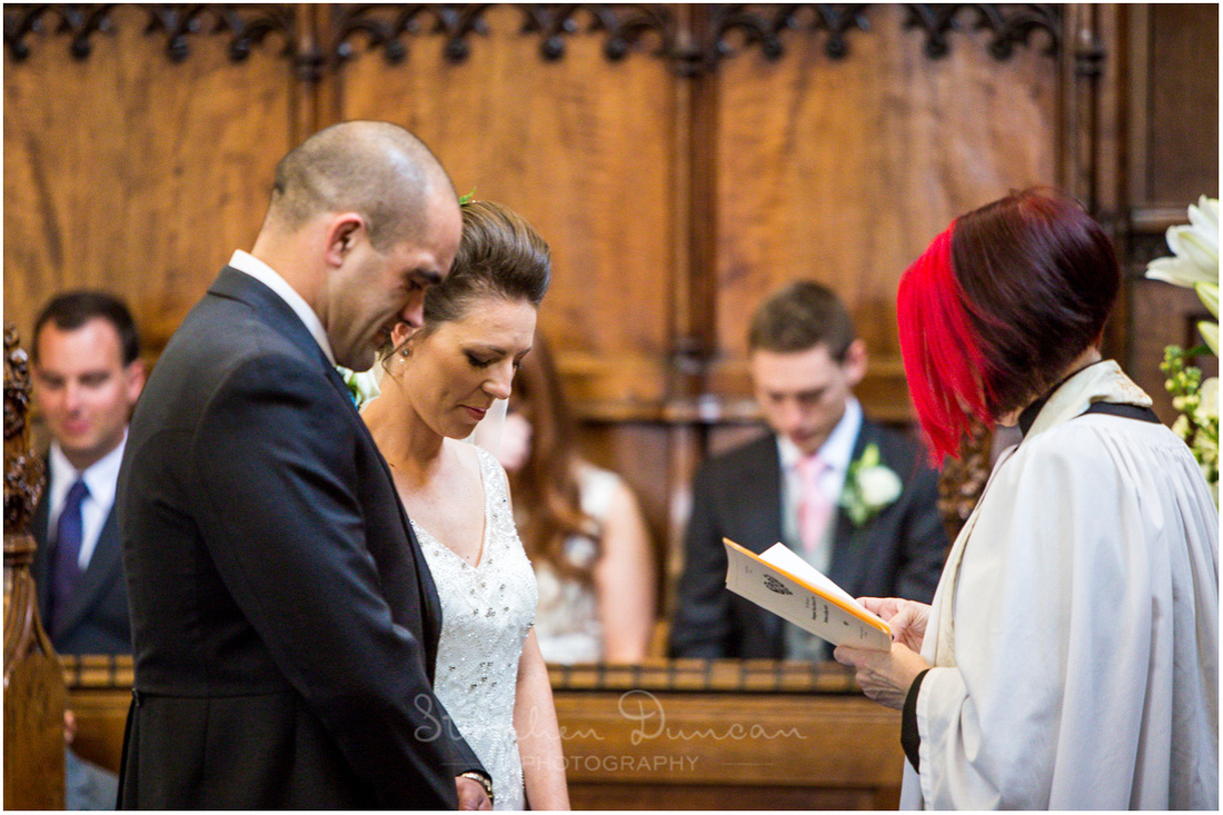 The bride and groom bow their heads as the marriage ceremony is erformed