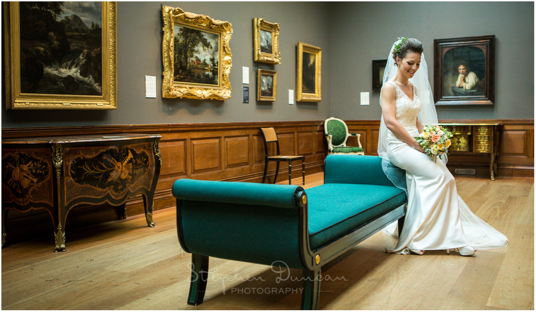 The bride perched on the arm of a chaise lungue in one of the gallery rooms