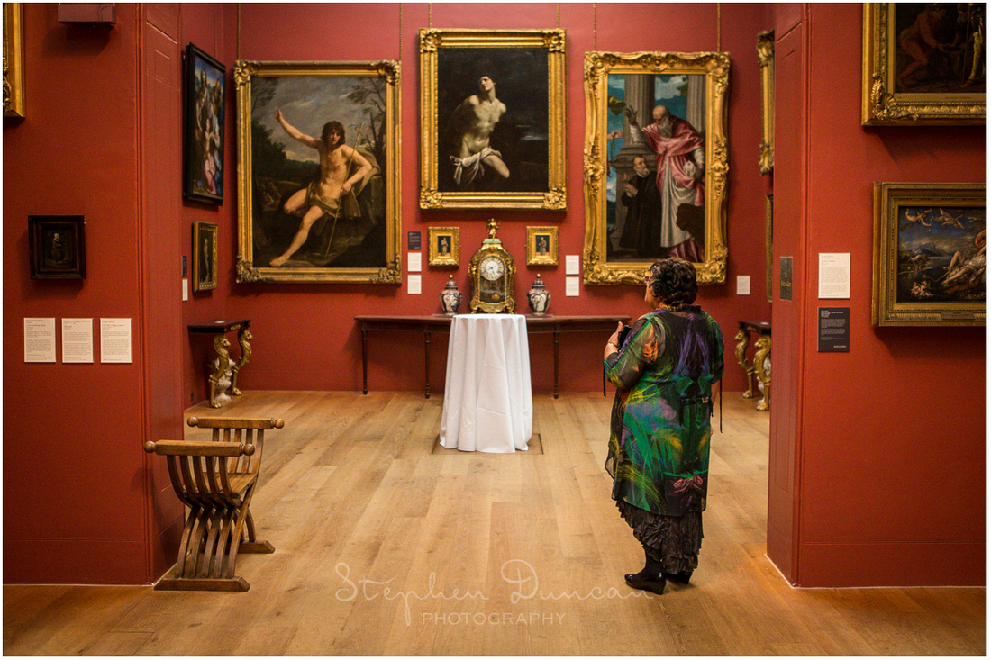 The groom's mother appreciates the art in the East wing of the gallery