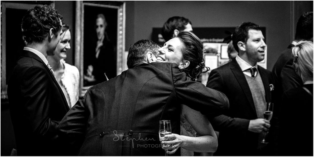 A wedding guest congratulates the bride with a hug