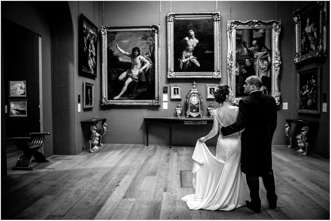 The newly married couple find some space to appreciate the art at their wedding reception