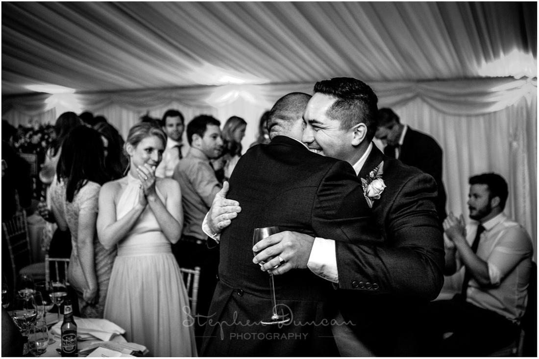 The groom congratulates the best man after his speech
