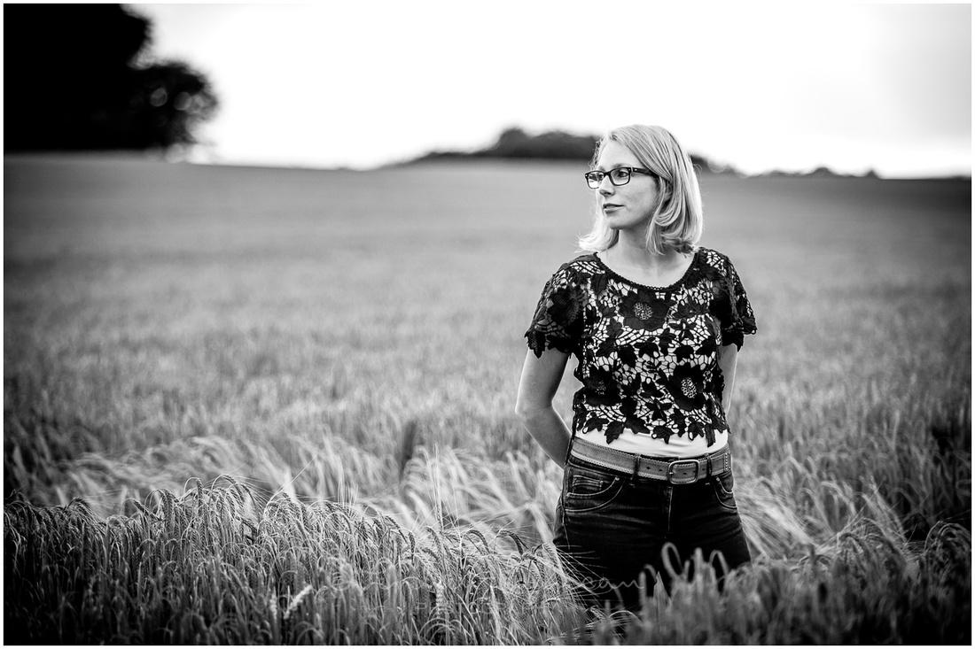 Bride portrait standing in cornfield black and white