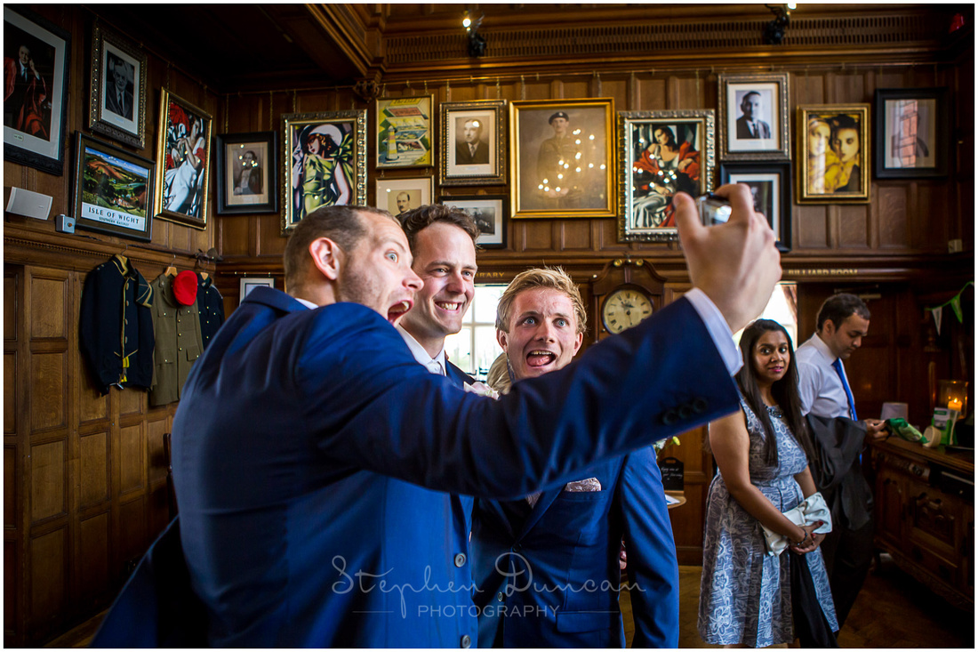Groom, best man and usher stop for a photograph in the main reception room of the Beach House Hotel