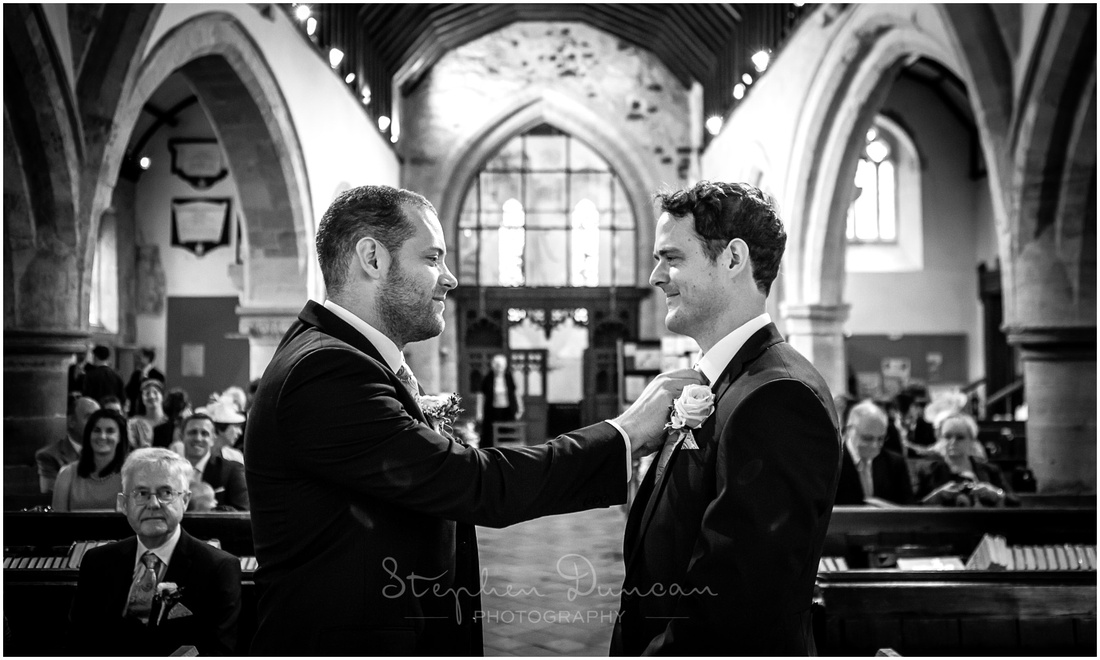 The best man casts a final eye over the groom to make sure that he's ready and presentable for his bride
