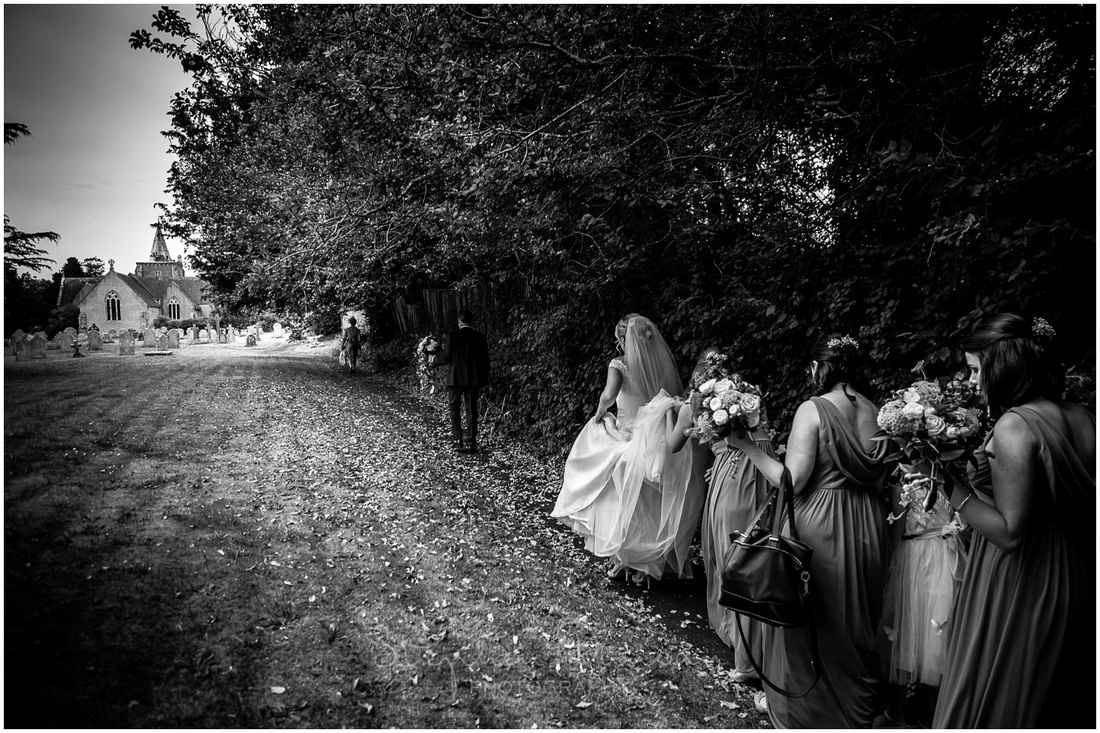 The bride walks through the grounds of the church with her bridal party