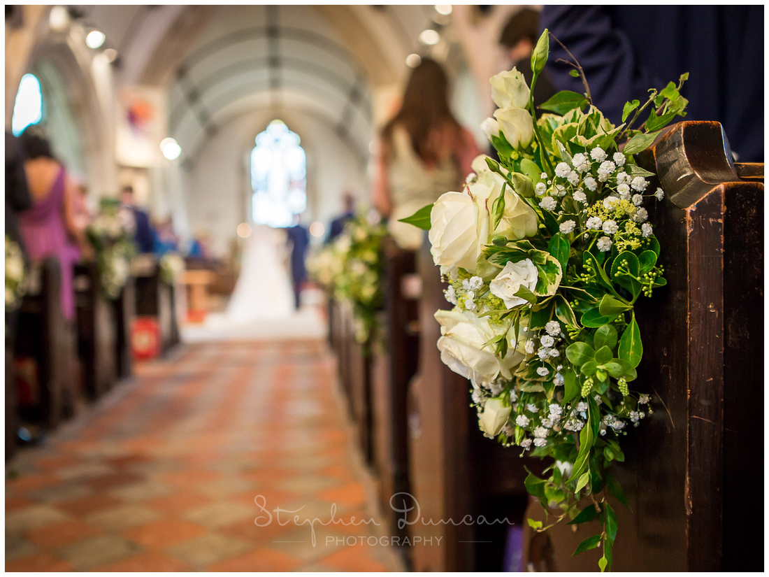 View of the flowers along the central aisle from the back of the church