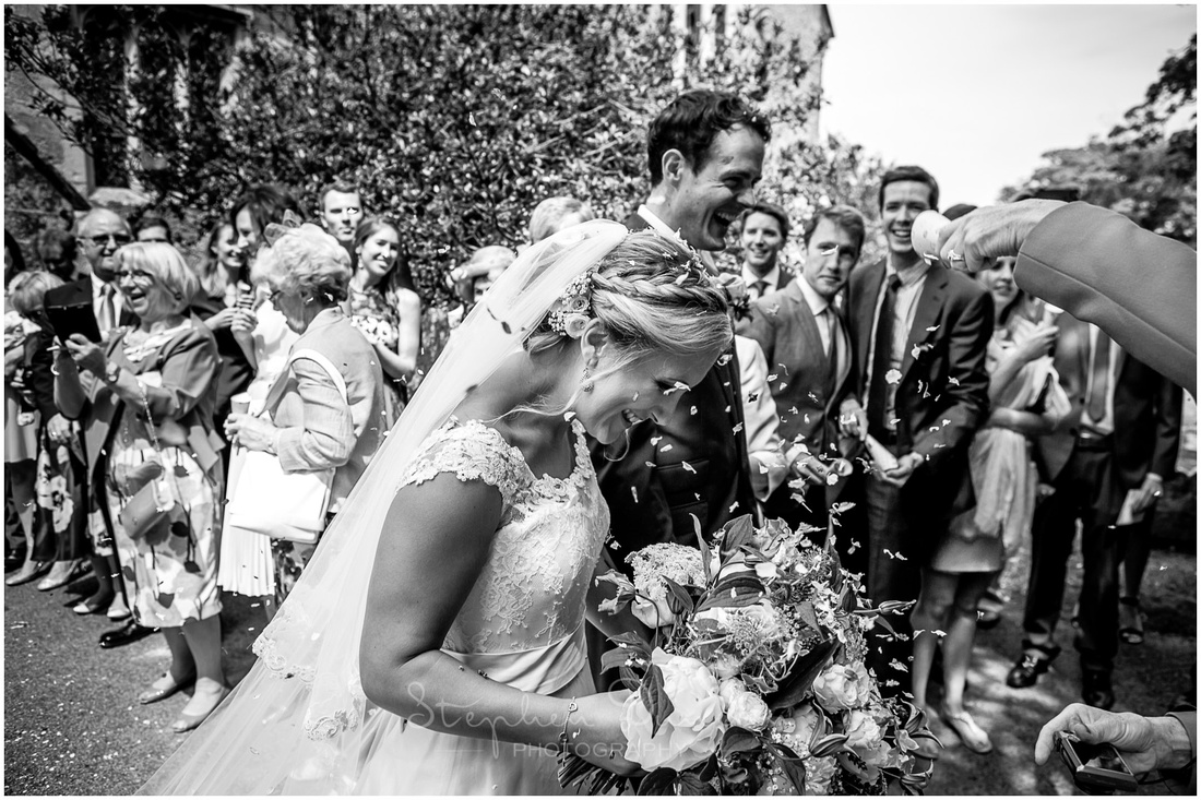 The bride and groom are received and congratulated by their guests in the grounds of the church