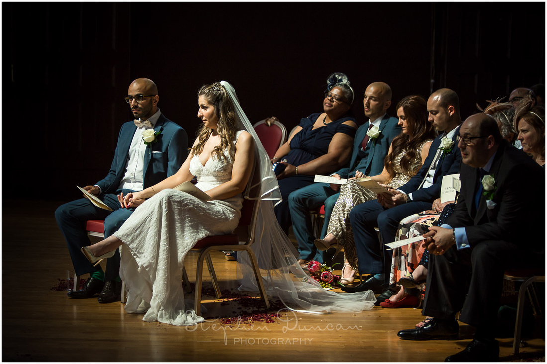 A natural shaft of light illuminates the bride and groom as they sit for part of the wedding ceremony