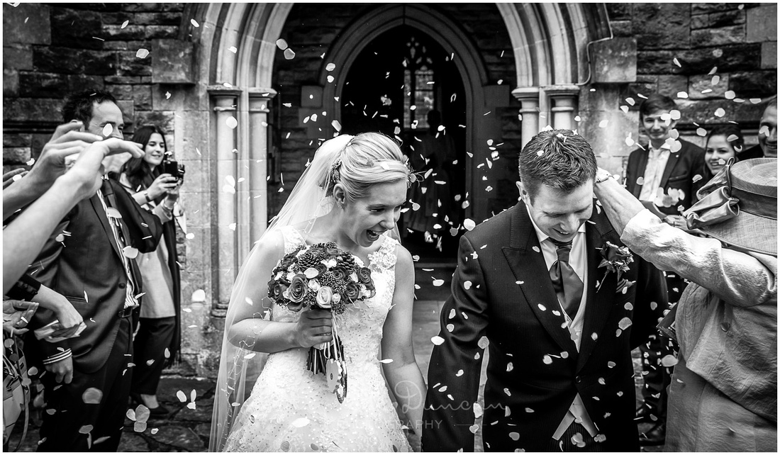 Bride and groom exit the church to a barrage of confetti from wedding guests