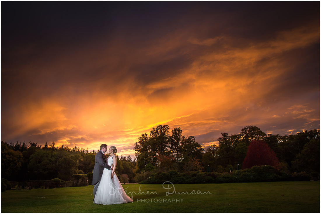 Stunning autumn sunset in New Forest with bride and groom