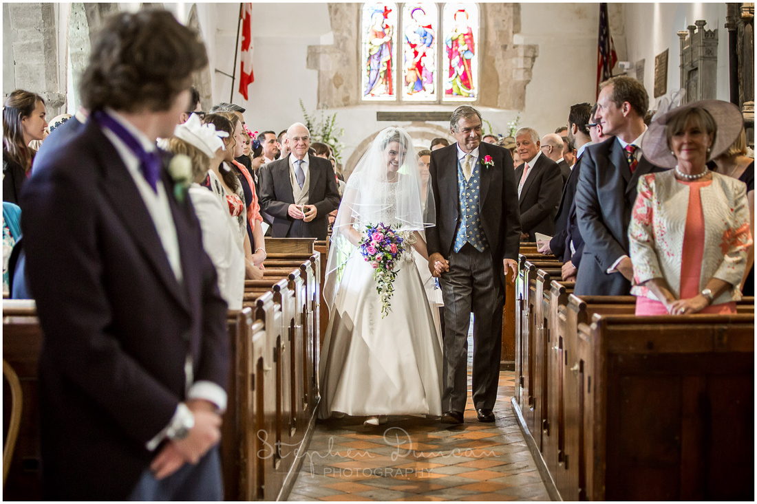 The groom turns to watch as his bride walks down the aisle on her father's arm