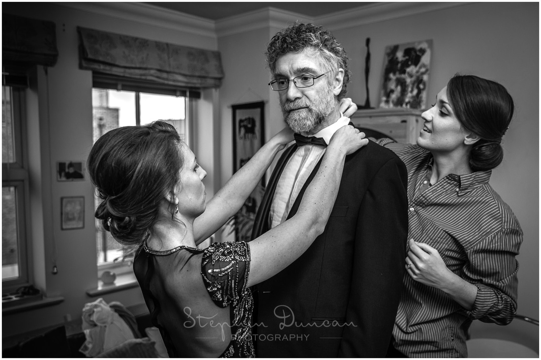 Bride and bridesmaid apply the finishing touches to the father of the bride's suit and tie