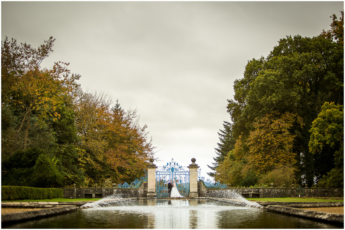 Couple by blue gates at end of lake in hotel gardens