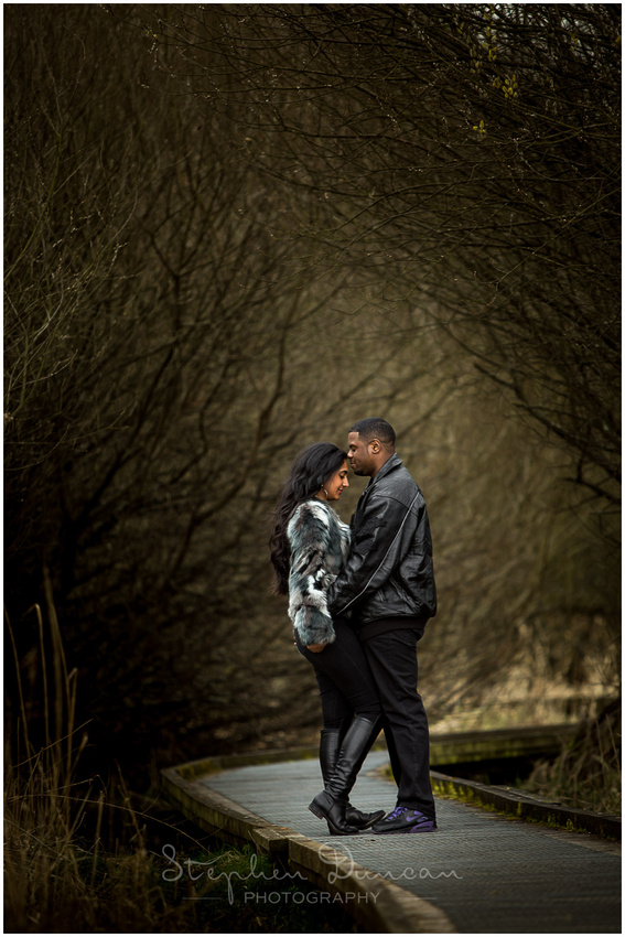 A couple stood by trees in nature reserve in WInchester