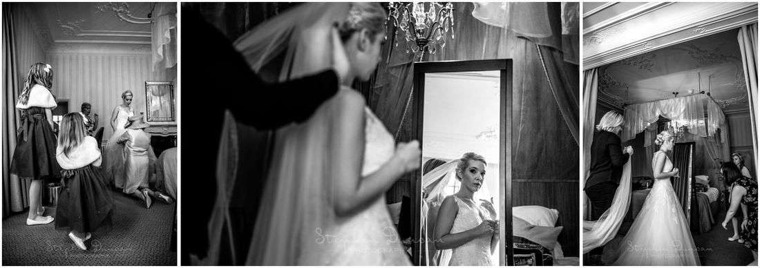 Finishing touches are applied to the bride in her dress and the veil is added