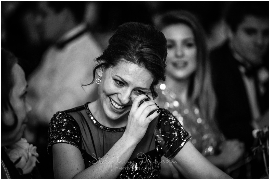 The bridesmaid wipes away a tear during the speeches