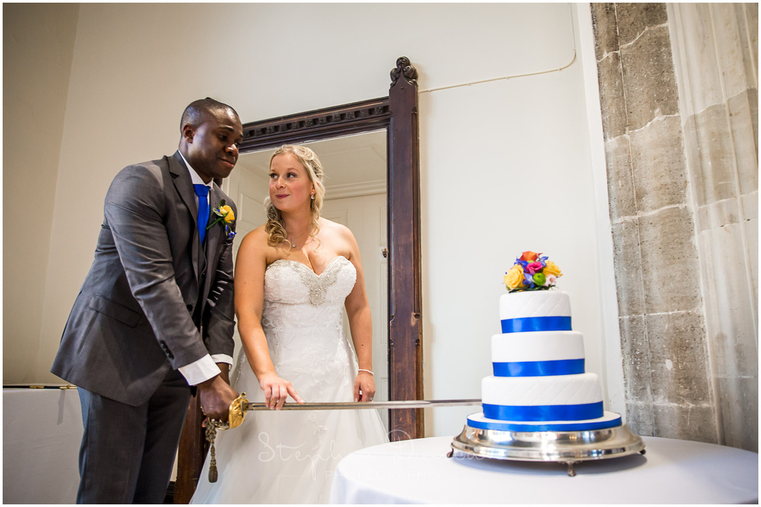 The bride and groom cut the cake with a sword