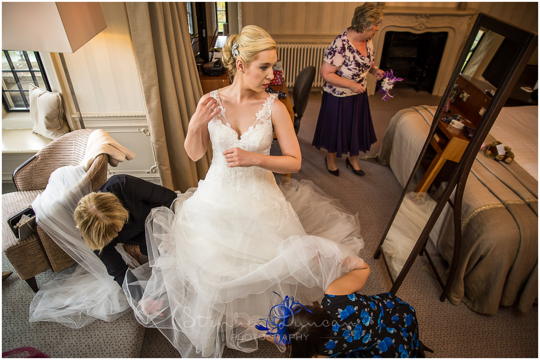The bride is helped into her wedding dress