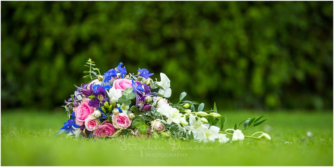 Detail shot of bride's bouquet in gardens of reception venue