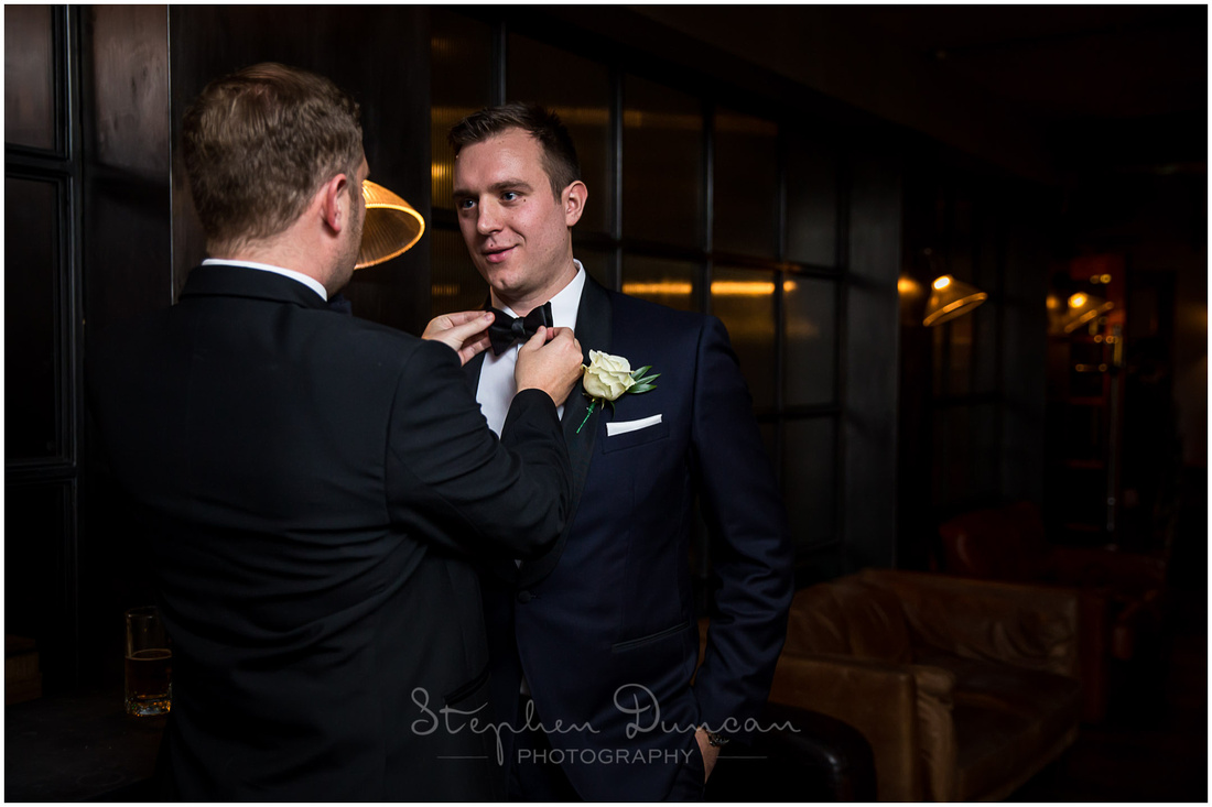 The groom, wearing a dark blue suit, with best man as he straightens the tie