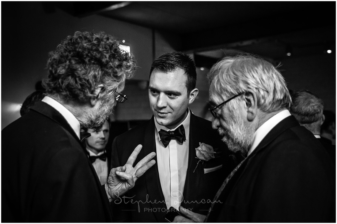 Black and white documentary photo of groom with guests