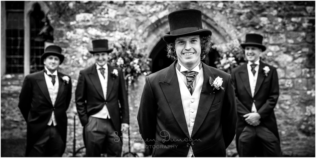 The groom stands outside the door to the church