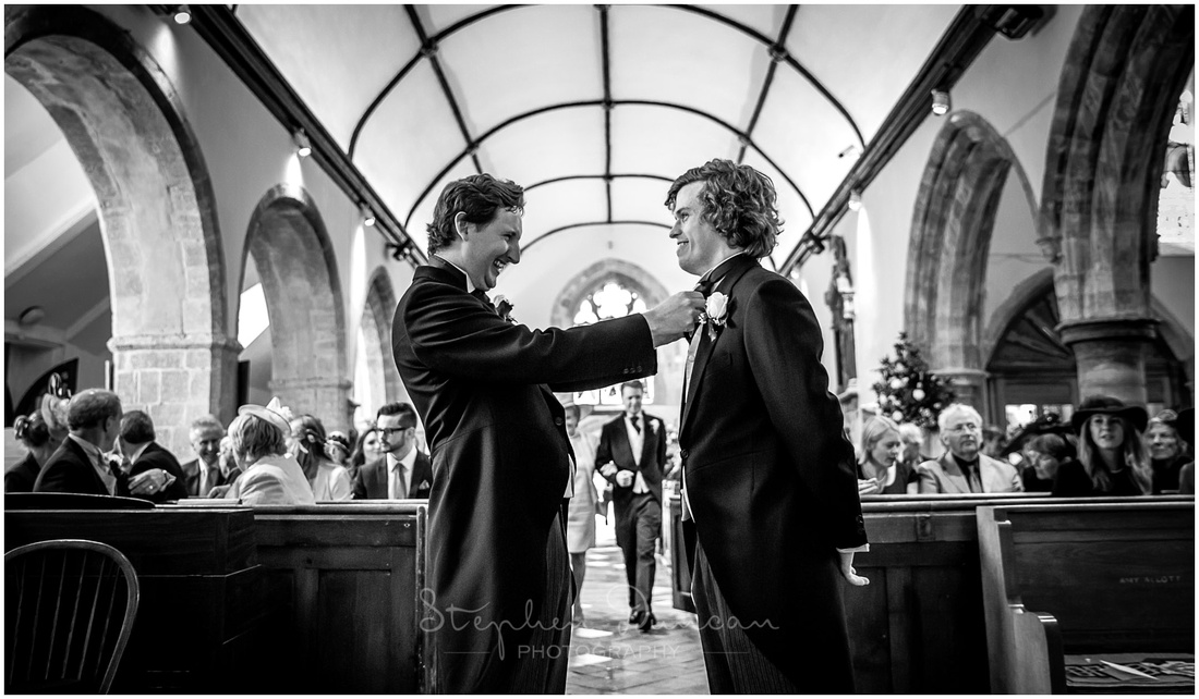 The best man gives the groom a final check to make sure that everything is in place ready for the wedding ceremony to begin