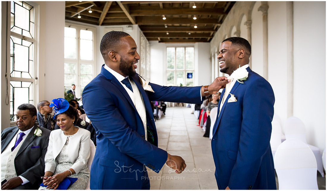 The best man adjusts the groom's tie before the start of the marriage ceremony