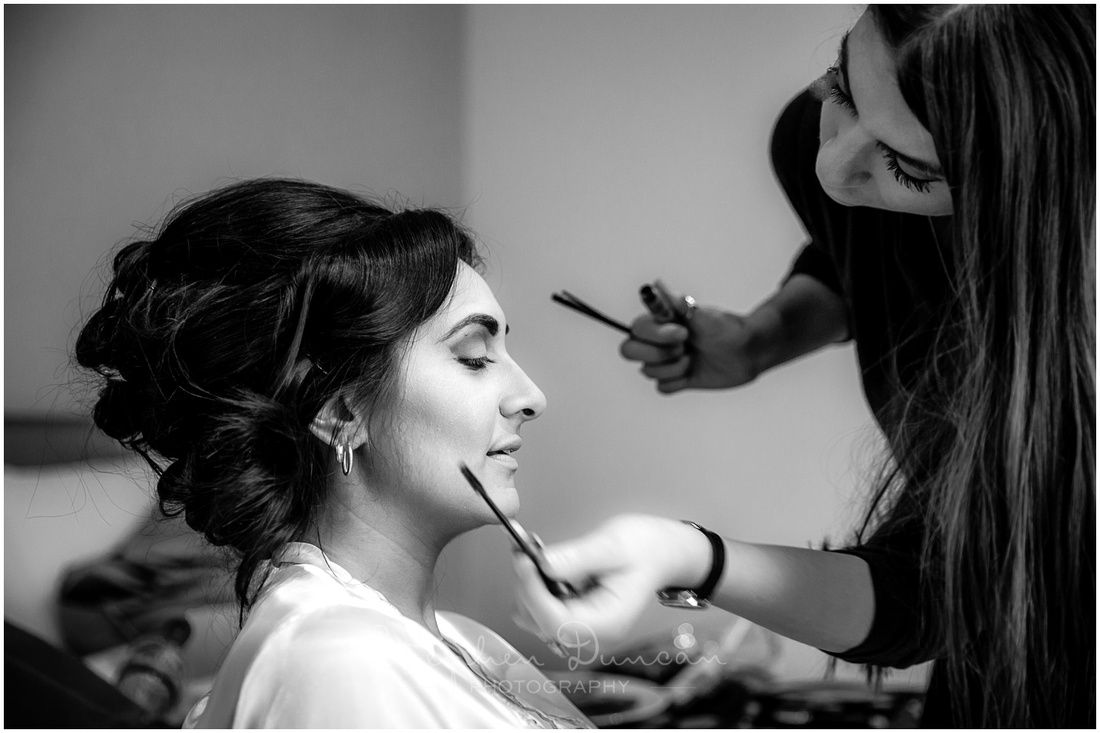 Black and white photo of bride applying make-up
