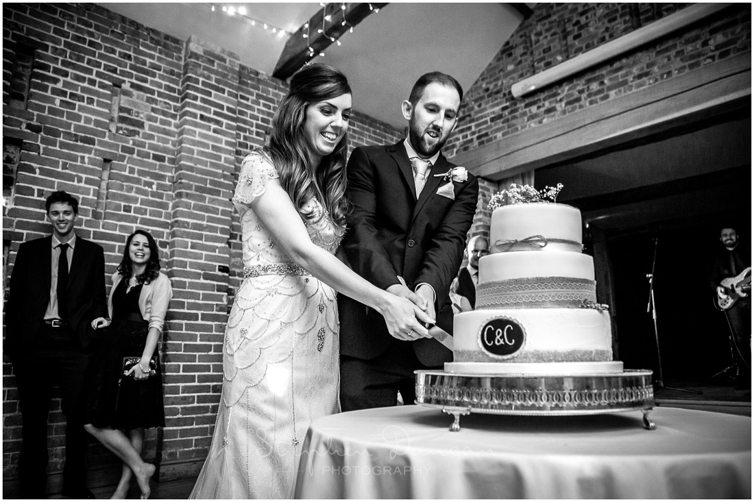 Bride and groom start the evening's celebrations by cutting the cake
