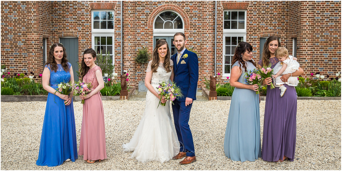Group photograph of bride and groom with bridesmaids