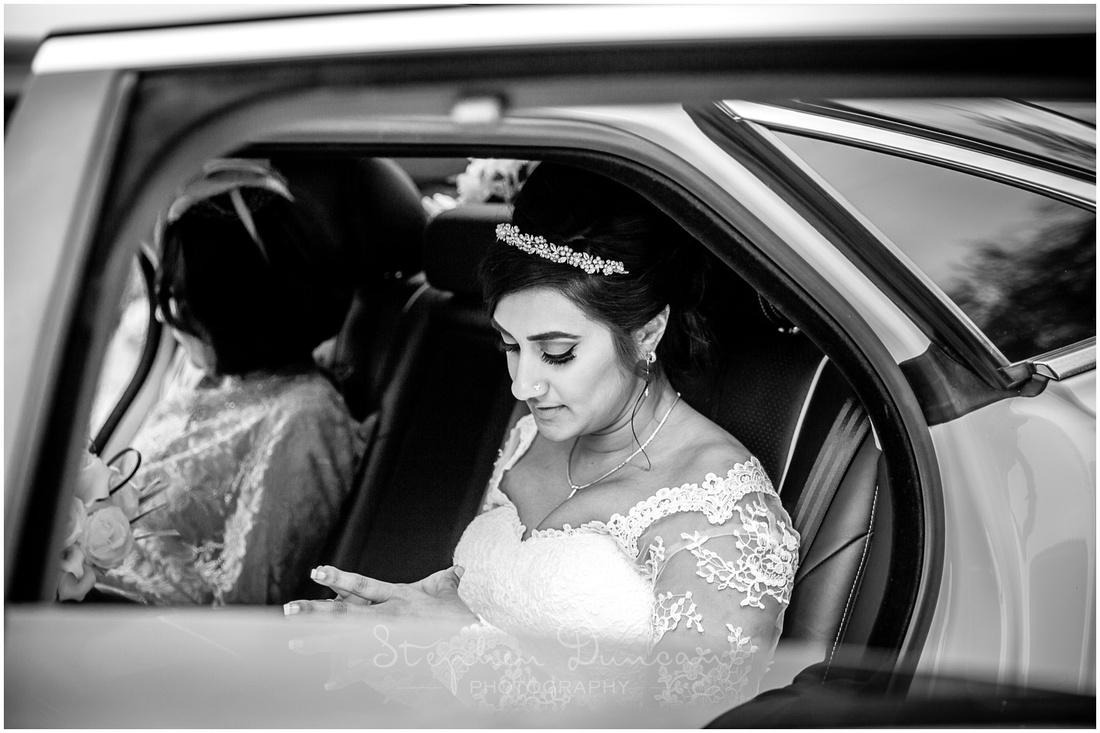 The bride gathers her thoughts before stepping out of the car to walk down the aisle