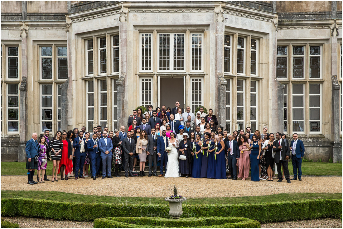 Wedding guests assembled on steps outside ceremony room at Highcliffe Castle in New Forest