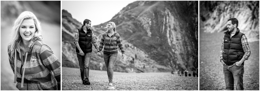 Couple walking along stony shore with cliffs in background