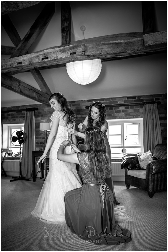 The bride is helped into her dress by her bridesmaids in the bridal suite at Wasing Park